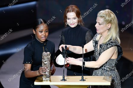 """Stock Image of French actress Fathia Youssouf (L) receives the Best Female Newcomer award for the movie """"Mignonnes"""" (Cuties) from French actress Isabelle Huppert (C) and French actress and Master of Ceremony Marina Fois 46th Cesar Film Awards 2021 ceremony at l'Olympia."""