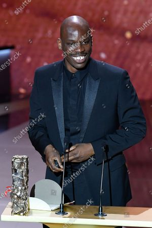 """French actor Jean-Pascal Zadi poses with his trophy after receiving the Best Male Newcomer award for the movie """"Tout simplement noir"""" (Simply Black) 46th Cesar Film Awards 2021 ceremony at l'Olympia."""