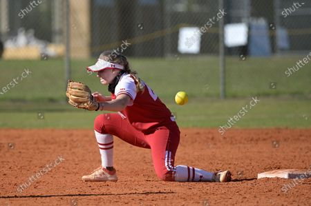Wisconsin infielder Lauren Foster (24) has a throw get past her during an NCAA college softball game against Michigan, in Leesburg, Fla
