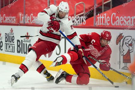 Carolina Hurricanes center Jordan Staal (11) and Detroit Red Wings center Dylan Larkin (71) battle for the puck in the first period of an NHL hockey game, in Detroit