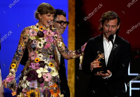 """Taylor Swift, from left, Jack Antonoff and Aaron Dessner accept the award for album of the year for """"Folklore""""at the 63rd annual Grammy Awards at the Los Angeles Convention Center on March 14 with both live and prerecorded segments"""