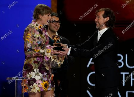 """Stock Image of Taylor Swift, from left, Jack Antonoff and Aaron Dessner accept the award for album of the year for """"Folklore""""at the 63rd annual Grammy Awards at the Los Angeles Convention Center on March 14 with both live and prerecorded segments"""