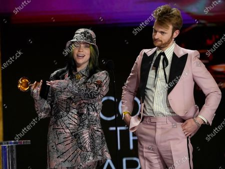 "Billie Eilish, left, and Finneas O'Connell accept the award for record of the year for ""Everything I Wanted"" at the 63rd annual Grammy Awards at the Los Angeles Convention Center"