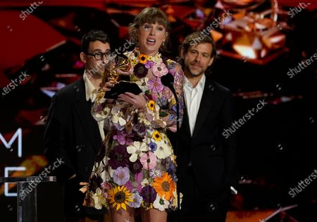 """Taylor Swift accepts the award for album of the year for """"Folklore""""at the 63rd annual Grammy Awards at the Los Angeles Convention Center. In background looking on are Jack Antonoff, left, and Aaron Dessner March 14 with both live and prerecorded segments"""