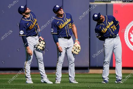 Stock Photo of Milwaukee Brewers' outfielders Garrett Mitchell, left, Tyron Taylor (15) and Corey Ray (78) wait during a pitching change in the fifth inning of a spring training baseball game against the Seattle Mariners, in Peoria, Ariz