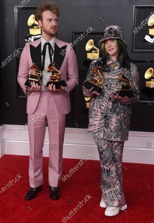 Finneas O'Connell, left, and Billie Eilish pose in the press room with the awards for best song written for visual media and record of the year at the 63rd annual Grammy Awards at the Los Angeles Convention Center