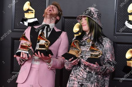 Finneas O'Connell, left, and Billie Eilish pose in the press room with the awards for best song written for visual media and record of the year at the 63rd annual Grammy Awards at the Los Angeles Convention Center on March 14 with both live and prerecorded segments