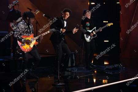 Host Trevor Noah (center) onstage with Black Pumas lead singer Eric Burton and Adrian Quesada(right) during a pre-taped segment for the 63rd Grammys at the LA Convention Center