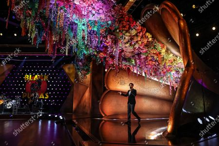 Trevor Noah emerges from a flower adorned gramophone during a pre-taped segment for the 63rd Grammys at the LA Convention Center