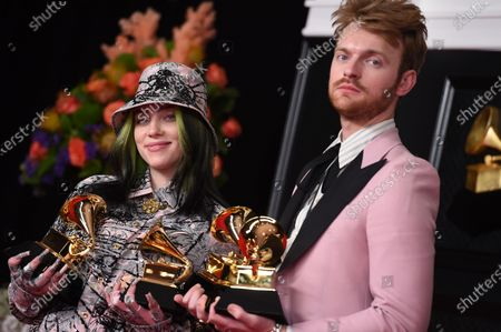 Stock Photo of Finneas O'Connell, left, and Billie Eilish pose in the press room with the awards for best song written for visual media and record of the year at the 63rd annual Grammy Awards at the Los Angeles Convention Center