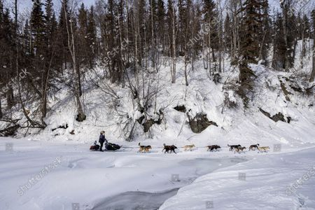Michelle Phillips mushes over an ice bridge on the Happy River, in Alaska,, during the Iditarod