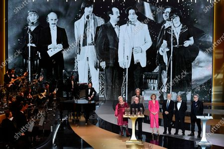 From left actress Josiane Balasko, French actor Thierry Lhermitte, French director and actor Michel Blanc, French actress Marie-Anne Chazel, French actor Gerard Jugnot, French actor Christian Clavier and French actor Bruno Moynot, from the Splendid theater, stand on stage next to French actress and Master of Ceremony Marina Fois and French actor Laurent Lafitte after receiving the Anniversary award during the 46th Cesar Award ceremony on in Paris.during the 46th Cesar Award ceremony on Friday, March 12, 2021 in Paris