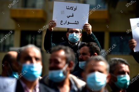 Parents of Lebanese students studying abroad carry a placard that reads in Arabic 'Our children in the streets' during a protest demanding the quick application of the student dollar law outside of Lebanese parliament speaker Nabih Berri house in Beirut, Lebanon, 15 March 2021. Parents are demanding to allow them to transfer dollars to their children studying abroad on the price of 1,515 Lebanese pounds instead of what the price is in the black market as the student dollar law will allow parents to transfer up to 10,000 dollars a year.