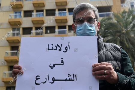 A parent of Lebanese students studying abroad carries a placard that reads in Arabic 'Our children in the streets' during a protest demanding the quick application of the student dollar law outside of Lebanese parliament speaker Nabih Berri house in Beirut, Lebanon, 15 March 2021. Parents are demanding to allow them to transfer dollars to their children studying abroad on the price of 1,515 Lebanese pounds instead of what the price is in the black market as the student dollar law will allow parents to transfer up to 10,000 dollars a year.