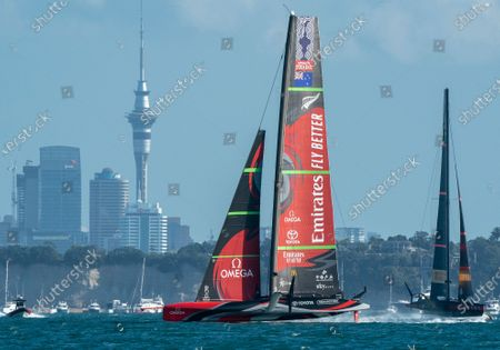 Defender's  Emirates Team New Zealand (ETNZ), skippered by Peter Burling on Te Rehutai and Italian challengers Luna Rossa Prada Pirelli, co-helmed by Jimmy Spithill and Francesco Bruni on Luna Rossa, race past the Auckland skyline during the last race of the 36th America's Cup. ETNZ won to retain the America's Cup.