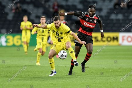 Tim Payne of Wellington Phoenix clears the ball under pressure from Bernie Ibini of Western Sydney Wanderers; Bankwest Stadium, Parramatta, New South Wales, Australia; A League Football, Western Sydney Wanderers versus Wellington Phoenix.
