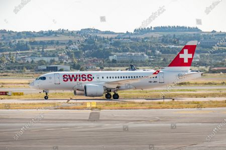 Stock Picture of Swiss International Air Lines Airbus A220-100 the former Bombardier CS100 aircraft as seen taxiing after landing in Thessaloniki International Airport Makedonia SKG LGTS in Greece. The narrow body regional airplane has the registration HB-JBH, the name Ascona and is powered by 2x PW jet engines. Swiss International Air Lines known as SWISS or Swiss Air Lines SWR LX is the flag carrier of Switzerland with hub in Zurich. The airline is member of Star Alliance aviation group and is owned by Lufthansa Group. The world passenger traffic declined during the coronavirus covid-19 pandemic era with the industry struggling to survive while passengers keep obligatory safety measures during the flights such as facemask, negative test and quarantine. Thessaloniki, Greece on October 12, 2020