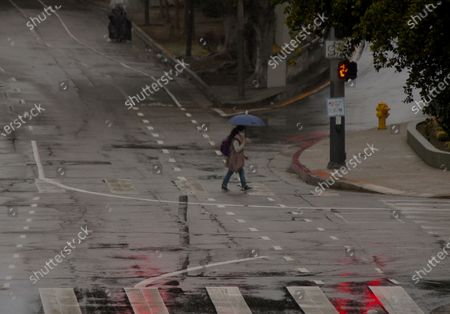 Stock Photo of Pedestrians walk under the rain on Figueroa St. under light rain downtown Los Angeles, . Another March storm moved through California on Monday, bringing snow to the Sierra Nevada, rain showers elsewhere and gale conditions offshore. Warnings for high winds blanketed a large portion of the interior of Southern California