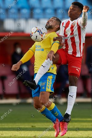 Alex Suarez Las Palmas and Largie Ramazani of Almeria compete for the ball during the La Liga Smartbank match between UD Almeria and UD Las Palmas at Estadio Juegos del Mediterraneo on February 14, 2021 in Almeria, Spain. Sporting stadiums around Spain remain under strict restrictions due to the Coronavirus Pandemic as Government social distancing laws prohibit fans inside venues resulting in games being played behind closed doors.