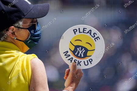 An usher holds a sign reminding fans to mask up while attending a spring training exhibition baseball game between the Philadelphia Phillies and the New York Yankees at George M. Steinbrenner Field in Tampa, Fla
