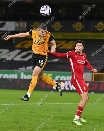 Wolverhampton Wanderers' Conor Coady heads the ball as Liverpool's Trent Alexander-Arnold watches during the English Premier League soccer match between Wolverhampton Wanderers and Liverpool at Molineux Stadium in Wolverhampton, England