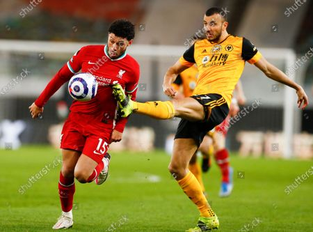 Wolverhampton Wanderers' Romain Saiss, right, and Liverpool's Alex Oxlade-Chamberlain battle for the ball during the English Premier League soccer match between Wolverhampton Wanderers and Liverpool at Molineux Stadium in Wolverhampton, England