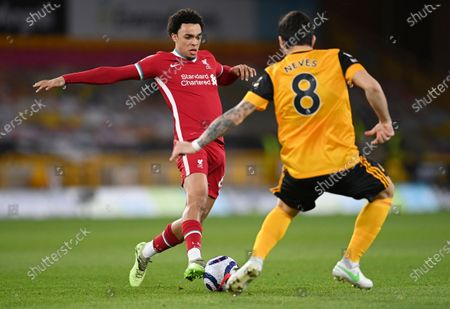 Liverpool's Trent Alexander-Arnold, left, takes the ball past Wolverhampton Wanderers' Ruben Neves during the English Premier League soccer match between Wolverhampton Wanderers and Liverpool at Molineux Stadium in Wolverhampton, England