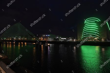 The Samuel Beckett Bridge and the Convention Centre in Dublin City are lit up green for the Saint Patrick's festival, Dublin, Ireland, 15 March 2021. For the second year running the festival will not take place due to COVID-19 restrictions. Saint Patrick's day is celebrated on 17 March. Ireland has temporaily postponed using the Astra-Zenica vaccine due to health concerns which has slowed down the pace of vaccination.