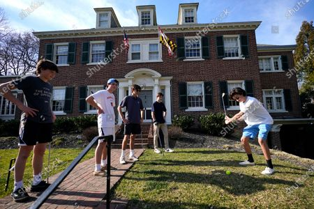 Aidan Roeca, right, tees off as friends, from left, Kent Lemken, Will Vincent, Ethan Chodnicki and Josh Peters look on while playing a game of golf with friends on a home's front yard during a warm winter day, in Baltimore. Maryland is expecting warm climate with temperatures reaching into the 60s this week