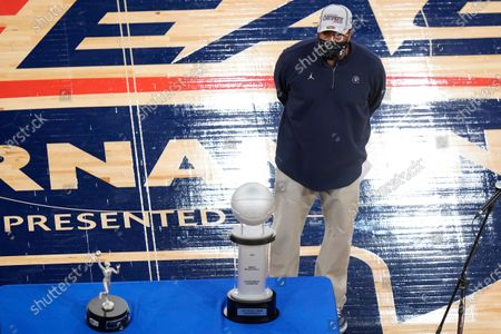 Georgetown head coach Patrick Ewing stands next to the tournament trophy after an NCAA college basketball game against Creighton in the championship of the Big East Conference tournament, in New York. Georgetown won 73-48