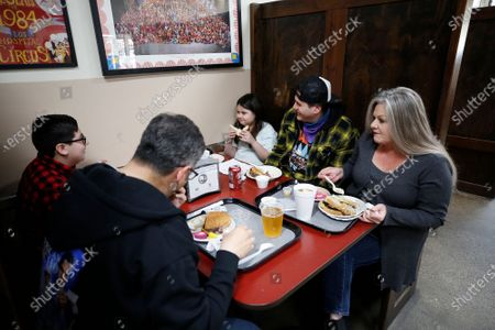 Stock Photo of Stacy Stevens, right, with son Nicholas Rivera, next, and grandchildren Roland Banuelos, 9, left, and sister Ruby Banuelos, 7, eat lunch at Philippe The Original near downtown Los Angeles on Monday. The restaurant is well known for continuously operating since 1908, making it one of the oldest restaurants in LA. L.A. County is reopening by permitting various businesses to reopen at a portion of their capacity. Phillip has been coming to Canter's Deli since it opened in the 1950's. Restaurants can open indoors at 25% capacity but must maintain eight feet of distance between tables. Indoor malls can operate at 50% capacity. Museums, zoos and aquariums may open indoors at 25% capacity; gyms, fitness centers and yoga and dance studios at 10% capacity; movie theaters at 25% capacity, with reserved, separated seating for groups; and retail and personal care services at 50% capacity. Philippe The Original on Monday, March 15, 2021 in Los Angeles, CA. (Al Seib / Los Angeles Times).