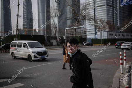 A man smokes as he walks in the street amid coronavirus pandemic in Beijing, China, 16 March 2021. China had administered 64.98 million doses of COVID-19 vaccines to the public, according to Li Bin, the deputy director of the National Health Commission said on a news briefing on 15 March 2021.