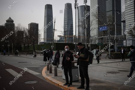 People stand in the street amid coronavirus pandemic in Beijing, China, 16 March 2021. China had administered 64.98 million doses of COVID-19 vaccines to the public, according to Li Bin, the deputy director of the National Health Commission said on a news briefing on 15 March 2021.