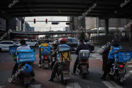 Food delivery men ride scooters in the street amid coronavirus pandemic in Beijing, China, 16 March 2021. China had administered 64.98 million doses of COVID-19 vaccines to the public, according to Li Bin, the deputy director of the National Health Commission said on a news briefing on 15 March 2021.