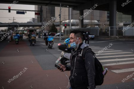 A man wearing protective face mask walks in the street amid coronavirus pandemic in Beijing, China, 16 March 2021. China had administered 64.98 million doses of COVID-19 vaccines to the public, according to Li Bin, the deputy director of the National Health Commission said on a news briefing on 15 March 2021.