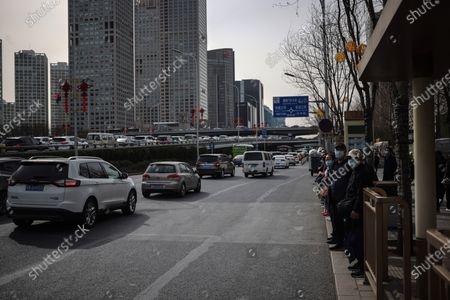 People wearing protective face masks wait for buses in the street amid coronavirus pandemic in Beijing, China, 16 March 2021. China had administered 64.98 million doses of COVID-19 vaccines to the public, according to Li Bin, the deputy director of the National Health Commission said on a news briefing on 15 March 2021.