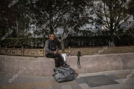 A homeless man is seen rests in the street amid coronavirus pandemic in Beijing, China, 16 March 2021. China had administered 64.98 million doses of COVID-19 vaccines to the public, according to Li Bin, the deputy director of the National Health Commission said on a news briefing on 15 March 2021.