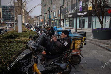 Stock Picture of A food delivery man rests on his scooter in the street amid coronavirus pandemic in Beijing, China, 16 March 2021. China had administered 64.98 million doses of COVID-19 vaccines to the public, according to Li Bin, the deputy director of the National Health Commission said on a news briefing on 15 March 2021.