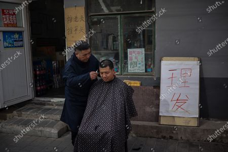 Stock Photo of A barber cuts hair for consumer amid coronavirus pandemic in Beijing, China, 16 March 2021. China had administered 64.98 million doses of COVID-19 vaccines to the public, according to Li Bin, the deputy director of the National Health Commission said on a news briefing on 15 March 2021.