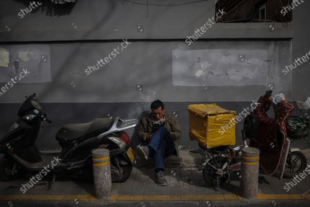 A man rests amid coronavirus pandemic in Beijing, China, 16 March 2021. China had administered 64.98 million doses of COVID-19 vaccines to the public, according to Li Bin, the deputy director of the National Health Commission said on a news briefing on 15 March 2021.