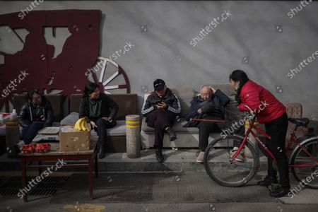 Stock Image of People rest and chat amid coronavirus pandemic in Beijing, China, 16 March 2021. China had administered 64.98 million doses of COVID-19 vaccines to the public, according to Li Bin, the deputy director of the National Health Commission said on a news briefing on 15 March 2021.