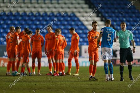 Tom Naylor of Portsmouth (4) and Mark Beevers of Peterborough United (5) shake hands before the match