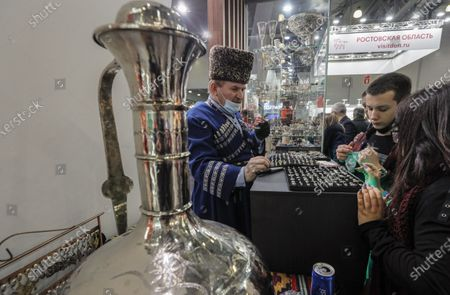 Stock Photo of Visitors examine jewellery on the Dagestan region pavilion at the 27th International Travel Show MITT at Crocus Expo Center in Moscow, Russia, 16 March 2021. MITT is the largest B2B travel and tourism trade show in Russia, attracting representatives of the Russian and the international tourism industry.