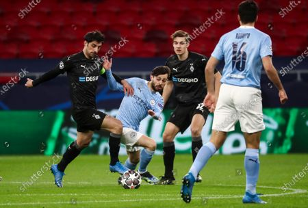 Lars Stindl of Borussia Monchengladbach, Bernardo Silva of Manchester City and Florian Neuhaus of Borussia Monchengladbach with Rodrigo of Manchester City looking on