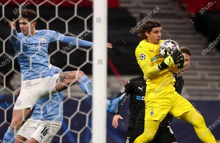 Yann Sommer goalkeeper of Borussia Monchengladbach saves ahead of John Stones of Manchester City