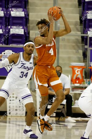 Texas forward Greg Brown (4) grabs a pass in front of TCU forward Kevin Easley (34) during the second half of an NCAA college basketball game in Fort Worth, Texas