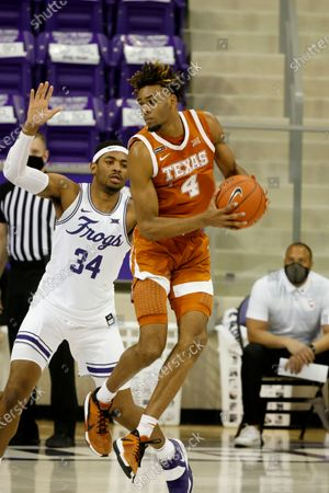 Stock Image of Texas forward Greg Brown (4) grabs a pass in front of TCU forward Kevin Easley (34) during the second half of an NCAA college basketball game in Fort Worth, Texas