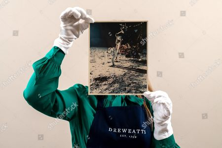 Sales Coordinator Lulu Randall holds up an original print of Buzz Aldrin as he erects the solar wind experiment on the surface of the moon with an estimated value of £1,500 - £2,500 ahead of auction today at Dreweatts Auction House in Newbury, Berks.  Neil Armstrong took the first photograph of Buzz Aldrin with his feet on the lunar surface on the 20th July 1969. The two black spots in the sky above the horizon and the foggy areas seen in the photograph were caused by the refraction of sunlight in the lens of Armstrong's camera.   Some of the most historic photographs chronicling the history of man's exploration of space, from early expeditions, to some of the latter trips of the 1990s will be sold at auction. Over 600 images, many of which capture historic moments, such as the first humans in space, the first spacewalk and the first moon landing will be auctioned today on March 17th 2021 as part of the Space Exploration Photography and Ephemera auction by Dreweatts