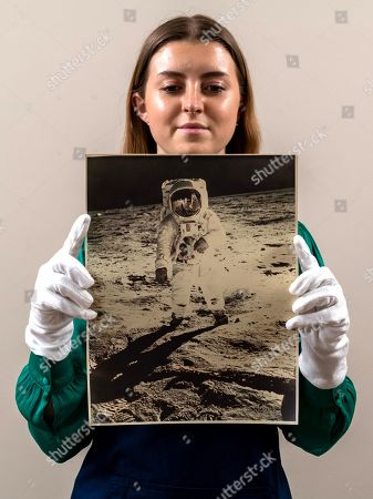 Sales Coordinator Lulu Randall holds up  an original print of Buzz Aldrin, taken by fellow astronaut Neil Armstrong in 1972 as part of the Apollo 11 moon landings with an estimated value of £2,000 - £3,000 ahead of auction today at Dreweatts Auction House in Newbury, Berks.  A rare front bodied portrait of Buzz Aldrin, taken by fellow astronaut Neil Armstrong is one of the most iconic images from the Apollo 11 mission. The reflection of Armstrong in this image makes it exceptionally rare. It was so breath-taking that it featured on the front cover of Time Magazine.  Some of the most historic photographs chronicling the history of man's exploration of space, from early expeditions, to some of the latter trips of the 1990s will be sold at auction. Over 600 images, many of which capture historic moments, such as the first humans in space, the first spacewalk and the first moon landing will be auctioned today on March 17th 2021 as part of the Space Exploration Photography and Ephemera auction by Dreweatts.