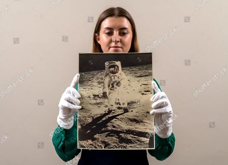 Stock Photo of Sales Coordinator Lulu Randall holds up  an original print of Buzz Aldrin, taken by fellow astronaut Neil Armstrong in 1972 as part of the Apollo 11 moon landings with an estimated value of £2,000 - £3,000 ahead of auction today at Dreweatts Auction House in Newbury, Berks.  A rare front bodied portrait of Buzz Aldrin, taken by fellow astronaut Neil Armstrong is one of the most iconic images from the Apollo 11 mission. The reflection of Armstrong in this image makes it exceptionally rare. It was so breath-taking that it featured on the front cover of Time Magazine.  Some of the most historic photographs chronicling the history of mans exploration of space, from early expeditions, to some of the latter trips of the 1990s will be sold at auction. Over 600 images, many of which capture historic moments, such as the first humans in space, the first spacewalk and the first moon landing will be auctioned today on March 17th 2021 as part of the Space Exploration Photography and Ephemera auction by Dreweatts.
